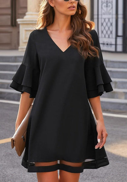 Front view of model wearing black flare sleeves mesh panel V-neckline shift dress
