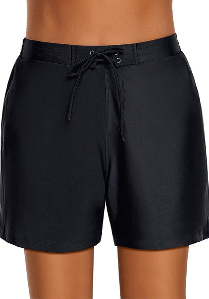 Front view of model wearing black lace-up board shorts