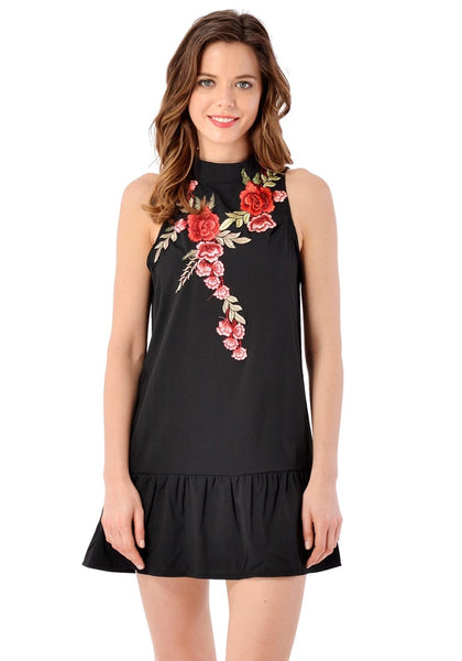 Front view of model wearing black mock neck floral embroidered dress
