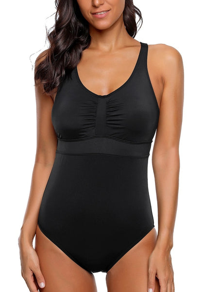 Front view of model wearing black ruched crisscross-back monokini