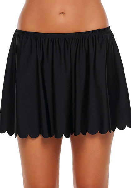 Front view of model wearing black scalloped hem swim skirt bottom