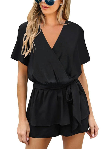Front view of model wearing black short sleeves layer belted surplice romper