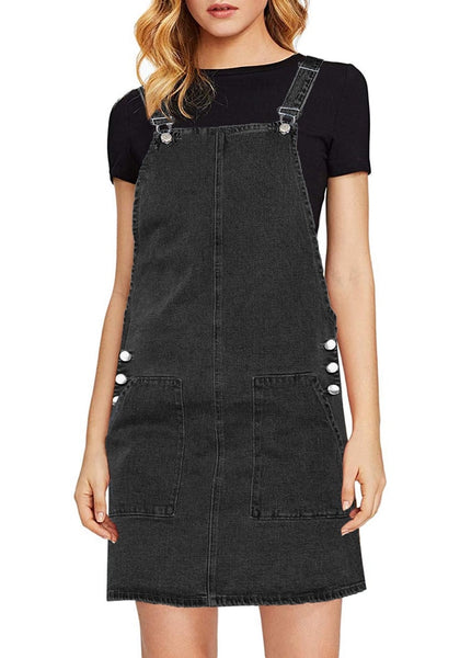 Front view of model wearing black side pockets overall denim pinafore dress