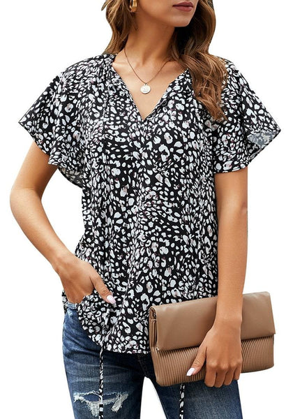 Front view of model wearing black tie-up neckline flared short sleeves printed top