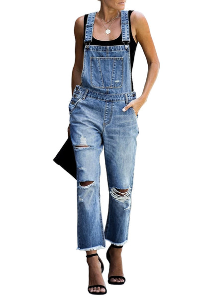 Front view of model wearing blue cropped raw hem ripped denim bib overall