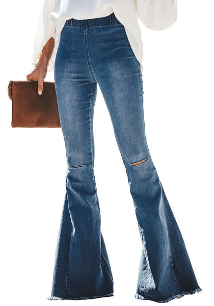 Front view of model wearing blue elastic-waist distressed denim bell bottom jeans