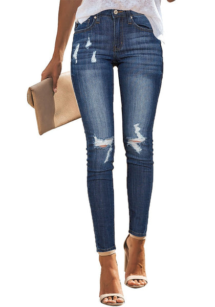 Front view of model wearing blue mid-rise ripped denim skinny jeans