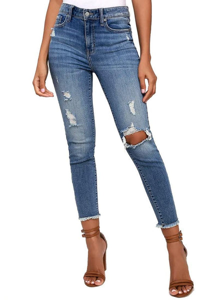 Front view of model wearing blue mid-rise skinny distress denim jeans