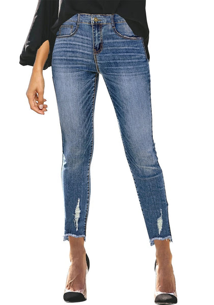 Front view of model wearing blue mid-waist raw hem  cropped ripped denim jeans