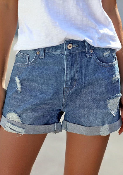 Front view of model wearing blue roll-over distressed denim shorts