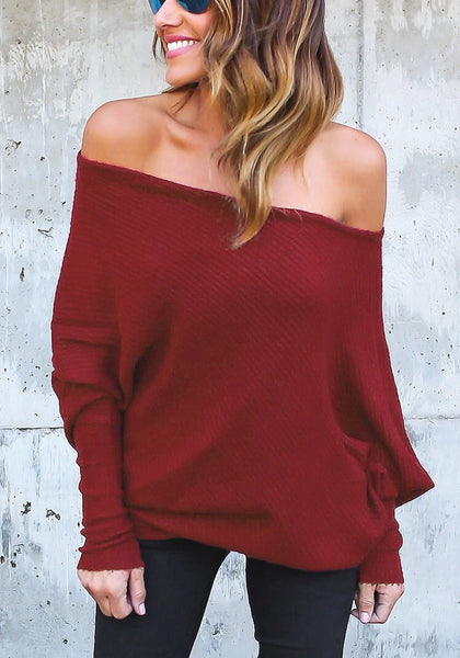 Front view of model wearing burgundy off-shoulder bat sleeves sweater