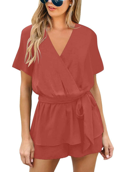 Front view of model wearing coral short sleeves layer belted surplice romper