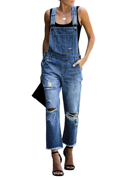 Front view of model wearing dark blue cropped raw hem ripped denim bib overall