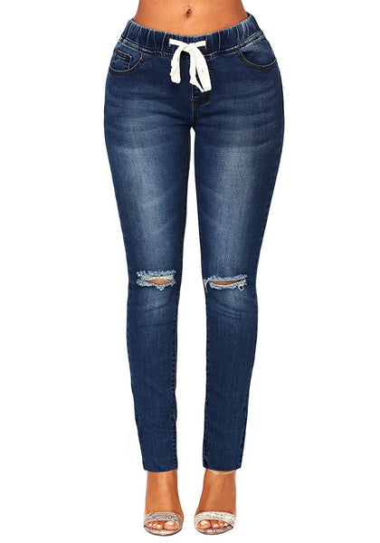 Front view of model wearing dark blue drawstring-waist washout ripped skinny jeans