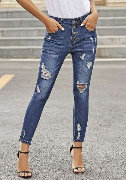 Front view of model wearing dark blue high-rise buttoned distressed denim skinny jeans