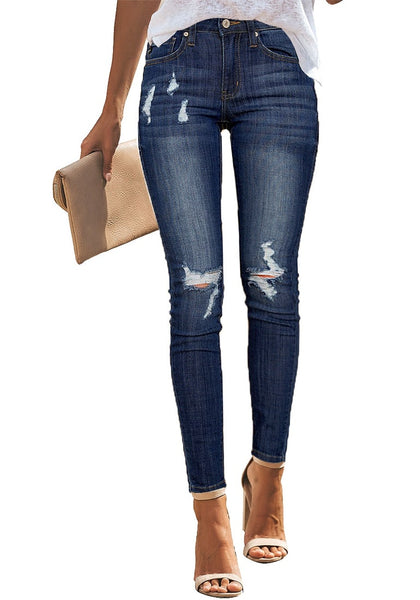 Front view of model wearing dark blue mid-rise ripped denim skinny jeans