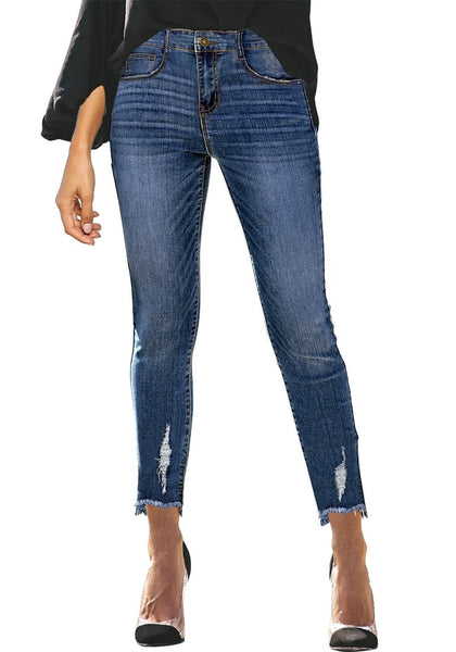 Front view of model wearing dark blue mid-waist raw hem  cropped ripped denim jeans