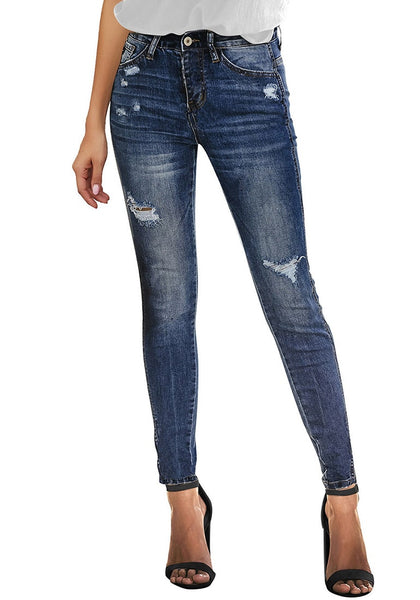 Front view of model wearing deep blue high-rise ripped skinny denim jeans