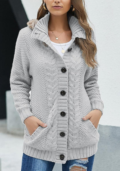 Front view of model wearing grey fur hooded collar button-up cable knit cardigan