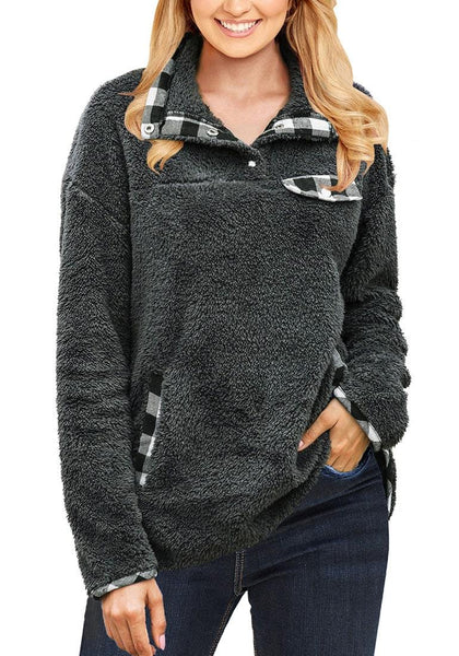 Front view of model wearing grey stand collar plaid trim fleece sweater
