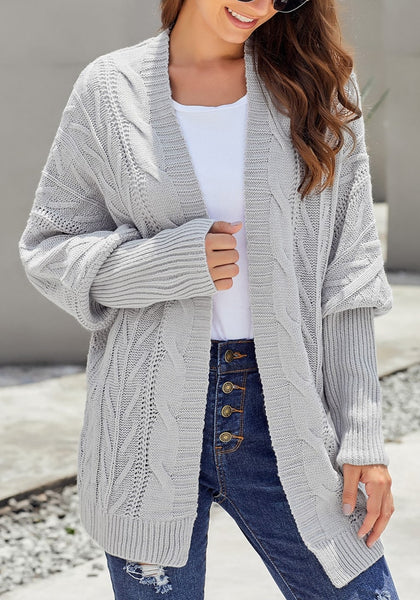 Front view of model wearing light grey open-front oversized cable knit cardigan