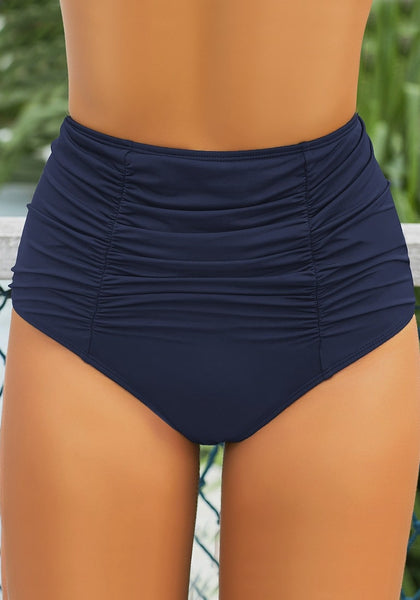 Front view of model wearing navy blue high-waist shirred swim bottom