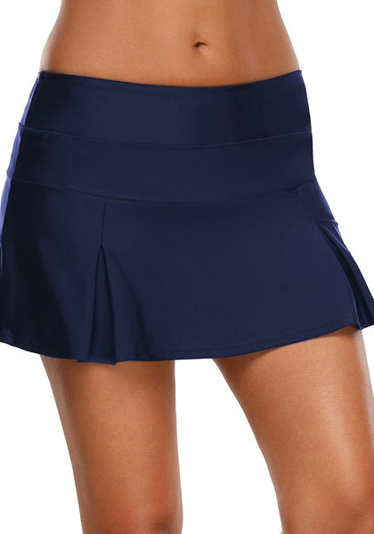 Front view of model wearing navy blue pleated mid-waist skirt