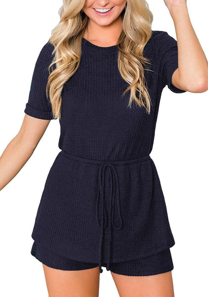 Front view of model wearing navy crew neck overlay drawstring knit romper