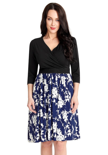 Front view of model wearing navy floral pattern surplice skater dress