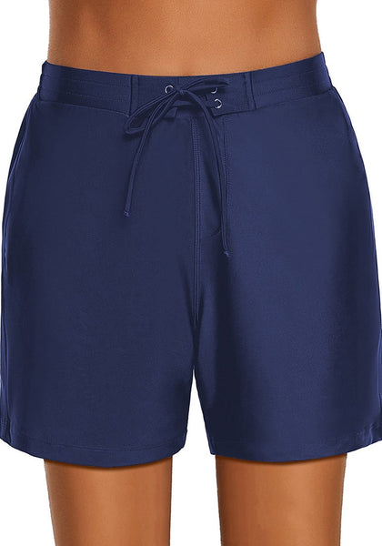Front view of model wearing navy lace-up board shorts