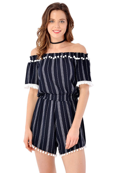 Front view of model wearing navy pompom off-shoulder romper