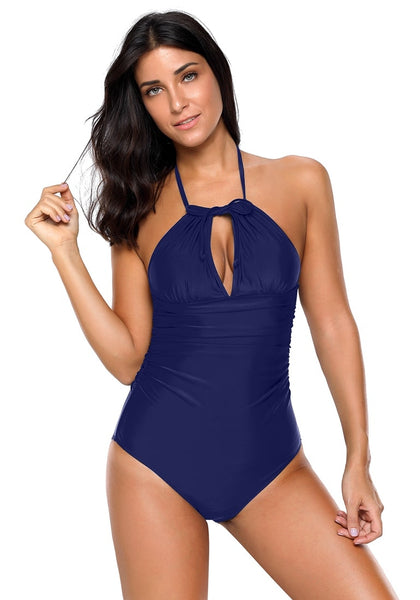 Front view of model wearing navy ruched convertible halter swimsuit