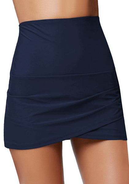 Front view of model wearing navy tulip hem high waist ruched swim skirt