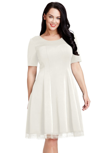 Front view of model wearing plus size off white short-sleeves skater dress