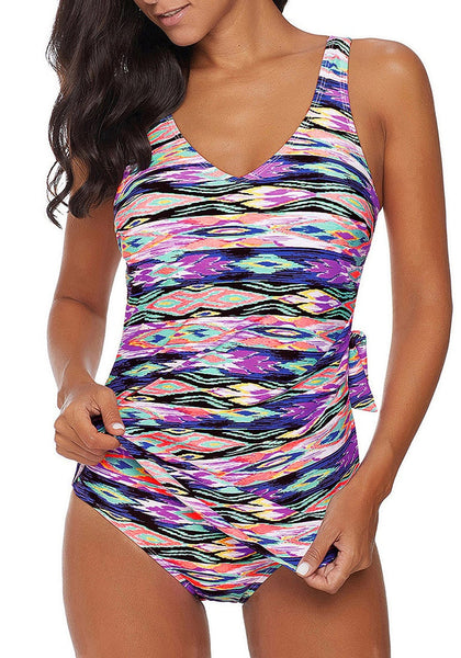 Front view of model wearing purple side-knot overlay abstract-print swimsuit