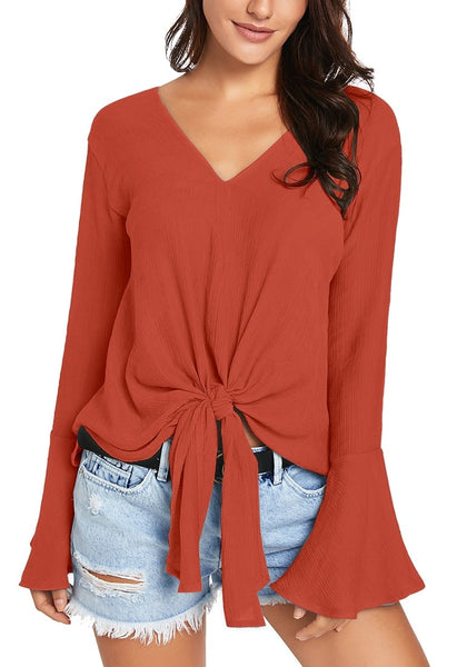 Front view of model wearing rust V-neck trumpet sleeves tie-front blouse