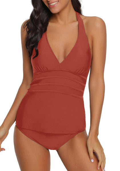 Front view of model wearing rust red solid color halter tankini set