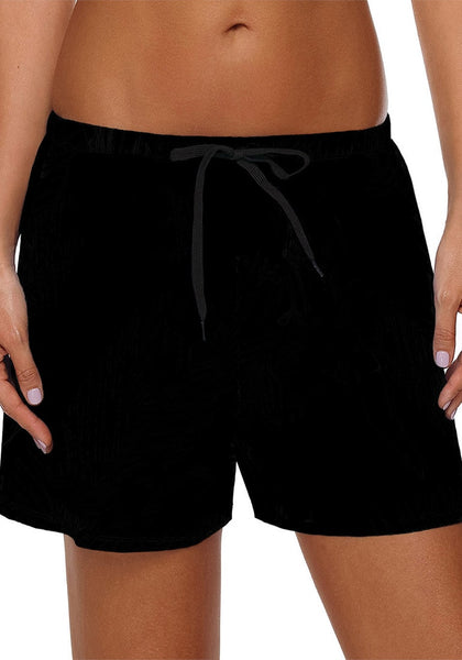 Front view of model wearing solid black drawstring board shorts