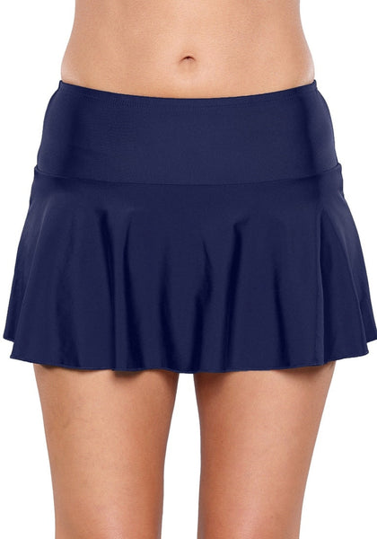 Front view of model wearing solid navy flared swim skirt