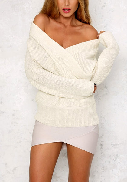 Front view of model wearing white wrap off-shoulder sweater with a mini skirt