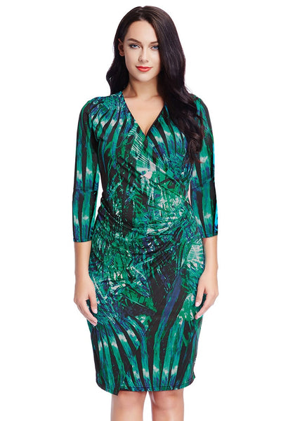 Front view of pretty model in plus size green leaf-printed midi wrap dress