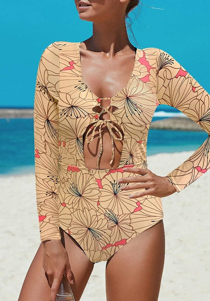 Front view of sexy model in tan cutout lace-up one-piece rash guard swimsuit