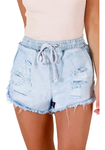 Front view of sexy model wearing light blue raw hem drawstring distressed denim shorts