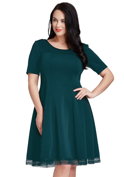Front view of woman in plus size deep green short-sleeves skater dress with left hand in the waist