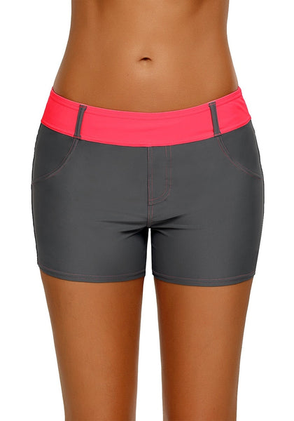 Front view of woman wearing grey color block neon pink waistband swim shorts