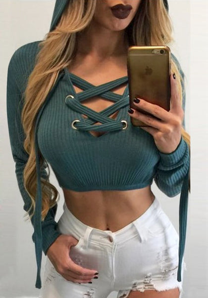 Front view of woman wearing pine green ribbed knit lace-up hooded crop top