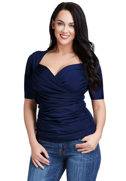 Frontal view of a model posing in a navy blue ruched surplice top