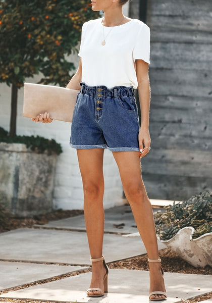 Front full body shot of model wearing dark blue elastic-waist button front roll-over denim shorts
