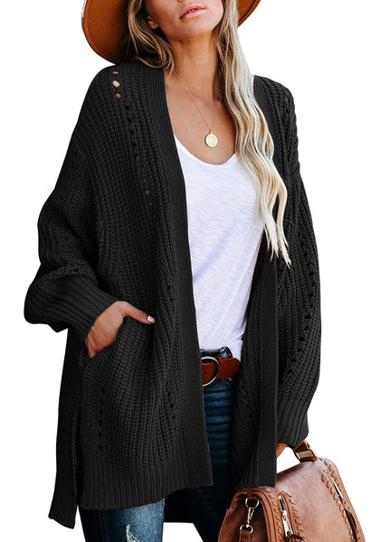 Front view of model wearing black open-front side slit oversized cable knit cardigan