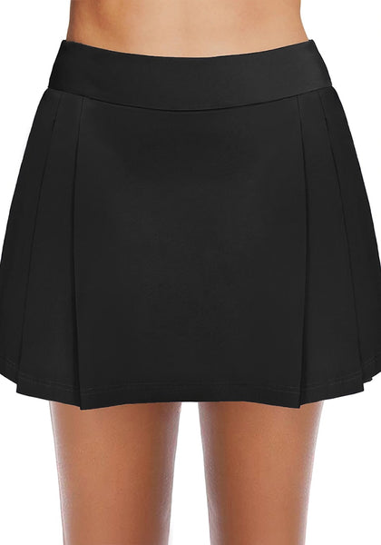 Front view of model wearing black pleated side mid-waist swim skirt